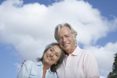 Portrait of a happy mature couple against sky smiling